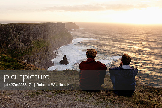 Two men sitting on The Cliffs of Moher, The Burren, County Clare, Ireland - p1427m2283171 by Roberto Westbrook