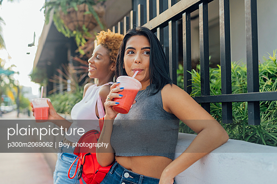 USA, Florida, Miami Beach, two female friends having a soft drink in the city - p300m2069062 by Boy photography