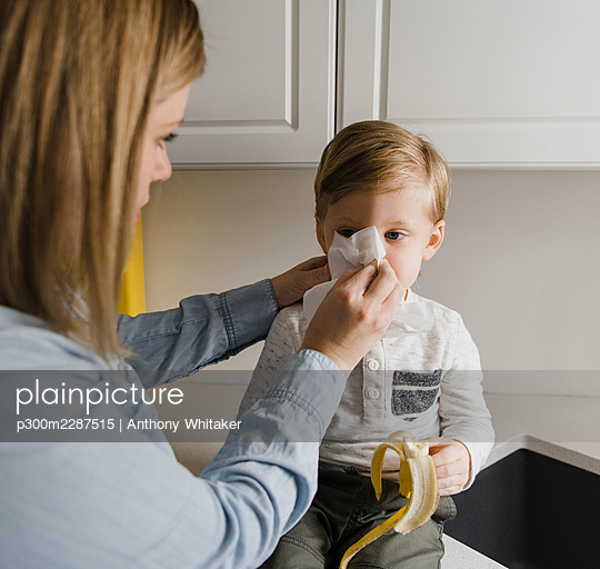 Mother cleaning son's nose at home - p300m2287515 by Anthony Whitaker