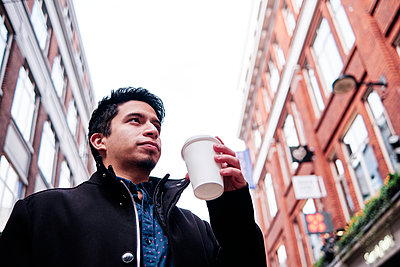 young latino guy holding a cup of coffee on the street - p1166m2234273 by Cavan Images
