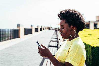 Portrait of black girl with afro hair and hoop earrings using her mobile phone in an urban space in the city. - p1166m2269559 by Cavan Images