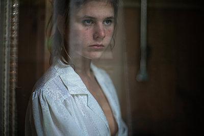 Junge Frau blickt aus dem Fenster - p1321m2223408 von Gordon Spooner