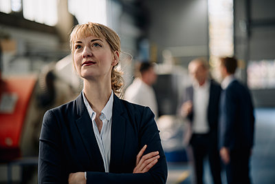 Portrait of a confident businesswoman in a factory with colleagues in backgound - p300m2171091 by Kniel Synnatzschke