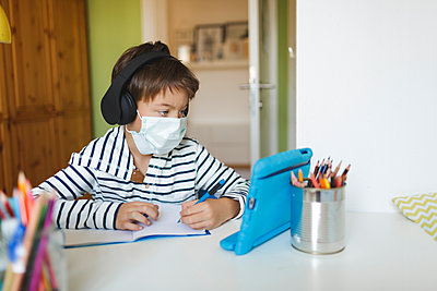Boy doing homeschooling and writing on notebook, using tablet and headphones, wearing mask at home during corona crisis - p300m2188830 by Epiximages