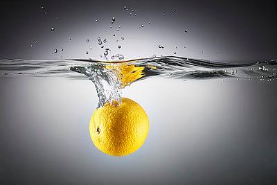 Close-up of lemon in splashing water - p301m1498743 by Larry Washburn
