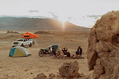 Motorcyclist road trippers around camp fire, Trona Pinnacles, California, US - p924m2068172 by Peter Amend
