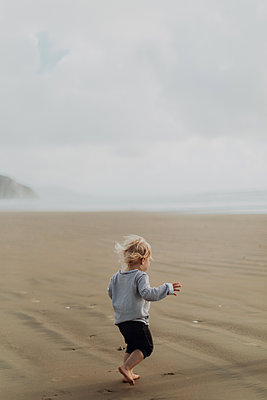 Toddler running on beach, Morro Bay, California, United States - p924m2127245 by Peter Amend
