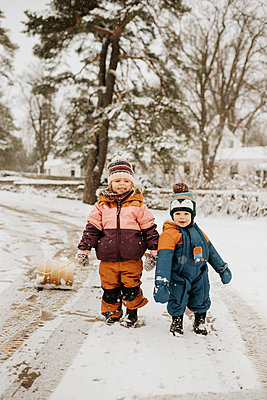 Brother (12-17 months) and sister (2-3) on snowy road - p924m2271219 by Sara Monika