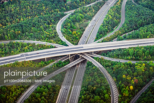 Aerial view of intersecting highways near trees, London, England,London, England - p1100m2084506 by Mint Images