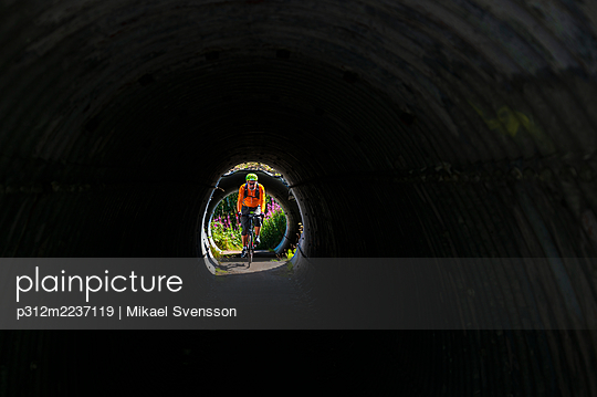 View of man cycling through tunnel - p312m2237119 by Mikael Svensson