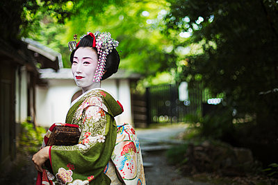 A woman dressed in the traditional geisha style, wearing a kimono and obi, with an elaborate hairstyle and floral hair clips, with white face makeup with bright red lips and dark eyes, side view outdoors.  - p1100m1185723 by Mint Images