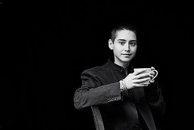 Portrait of sitting short-haired young woman holding cup of coffee - p300m2083419 by Jo Kirchherr