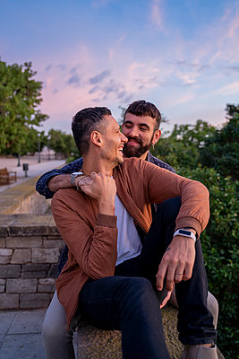 Happy affectionate gay couple sitting on a wall at sunset - p300m2155131 by VITTA GALLERY