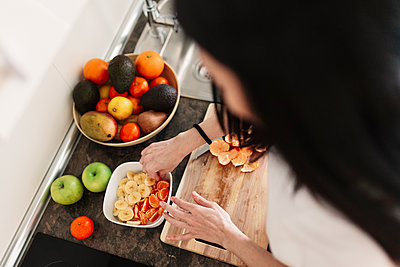 Woman preparing bowl of fruits on kitchen counter at home - p300m2276947 by Manu Reyes