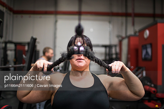 Strong woman training triceps muscle in gym - p1166m2111606 by Cavan Images