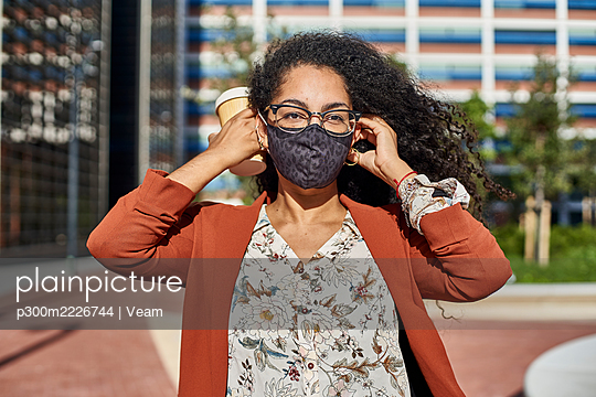 Young woman wearing protective face mask standing in city on sunny day - p300m2226744 by Veam