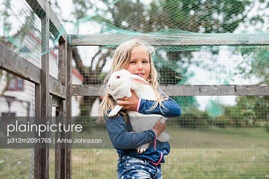 Girl holding rabbit - p312m2091765 by Anna Johnsson