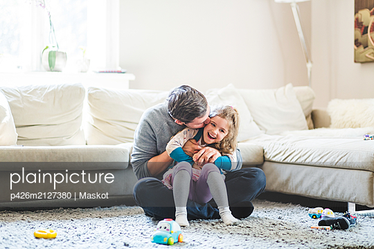 Mid adult man kissing daughter while sitting on carpet at home - p426m2127380 by Maskot