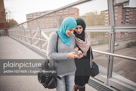 Two female friends on footbridge reading smartphone texts - p429m1021693f by Eugenio Marongiu