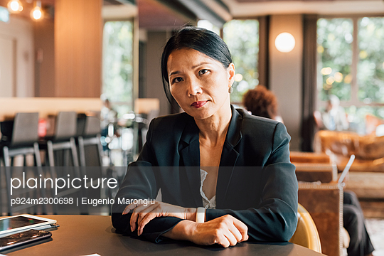 Italy, Portrait of businesswoman sitting at table in creative studio - p924m2300698 by Eugenio Marongiu