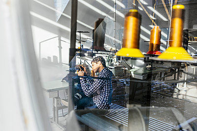 Young male tailor sewing jeans in factory - p1185m994372f by Astrakan