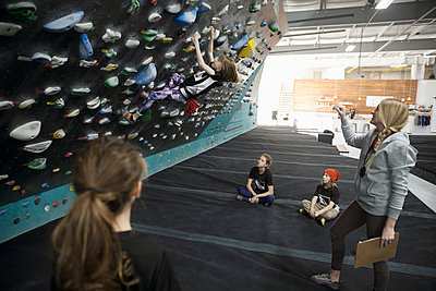 Female instructor teaching girl rock climber students at climbing wall in climbing gym - p1192m1560051 by Hero Images