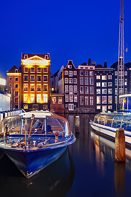 Netherlands, rth Holland, Amsterdam, Tourboats moored in old town harbor at night - p300m2197146 by Artur Bogacki
