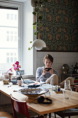 Teenage boy using mobile phone while studying at home - p426m2101635 by Maskot