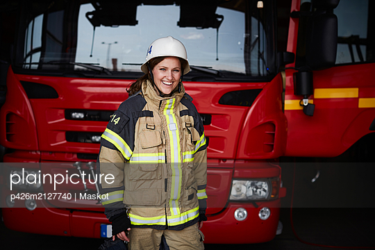 Portrait of smiling female firefighter standing in front of fire engine at fire station - p426m2127740 by Maskot