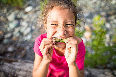 Girl eating cucumber - p1166m2202046 by Christopher Kimmel / Alpine Edge Photography