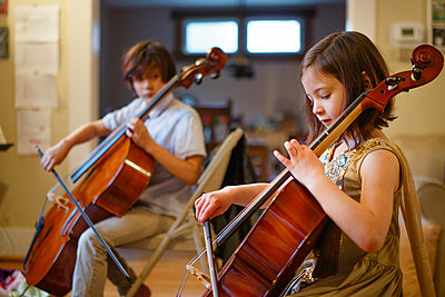 A brother and sister practice cello together in their living room - p1166m2205714 by Cavan Images