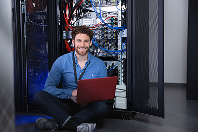 Smiling male IT professional with laptop sitting cross legged in front of server rack - p300m2274625 by Florian Küttler