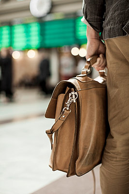 Midsection of businessman carrying bag while standing on railway station - p426m844670f by Maskot