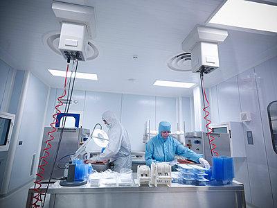 Scientists work in laboratory clean room - p42912954f by Monty Rakusen