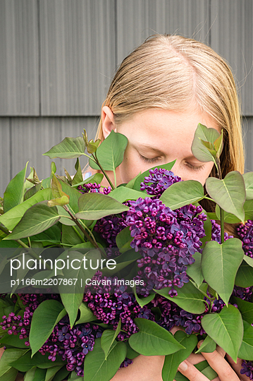 Close Up of Young Girl Holding a Bunch of Lilac Flowers - p1166m2207867 by Cavan Images