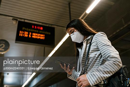 Female passenger using phone while waiting at railroad station - p300m2240331 by Ezequiel Giménez