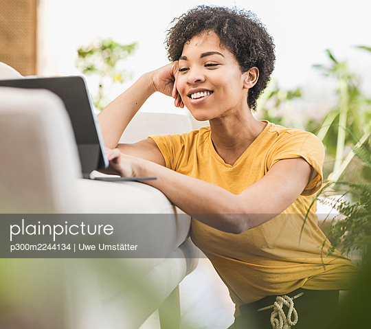 Young woman smiling while using digital tablet sitting at home - p300m2244134 by Uwe Umstätter