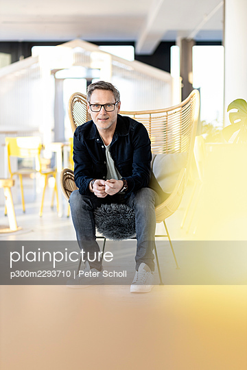 Mature businessman wearing eyeglasses siting on wicker chair in office - p300m2293710 by Peter Scholl