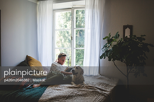 Full length of retired man reading book while resting with dog on bed at home - p426m2046382 by Maskot