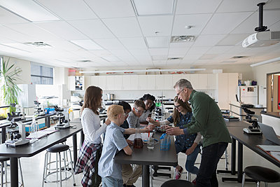 Teacher and middle school students conducting scientific experiment in science laboratory - p1192m1473269 by Hero Images