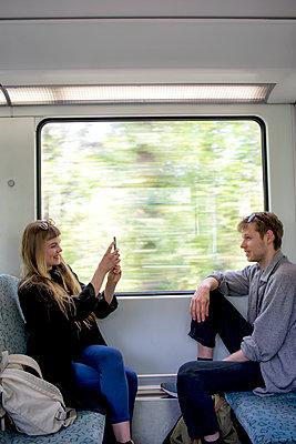 Junge Frau fotografiert jungen Mann in der Bahn - p1212m1138824 von harry + lidy