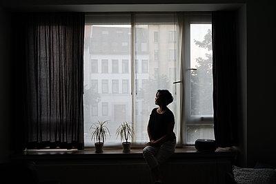a woman sitting by a window - p1610m2284079 by myriam tirler
