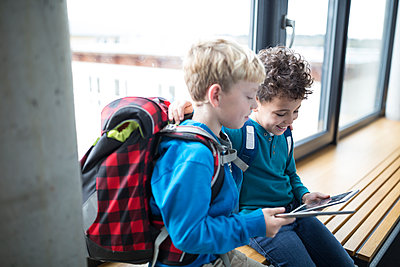 Smiling pupils sharing a tablet on school corridor - p300m2005298 von Fotoagentur WESTEND61