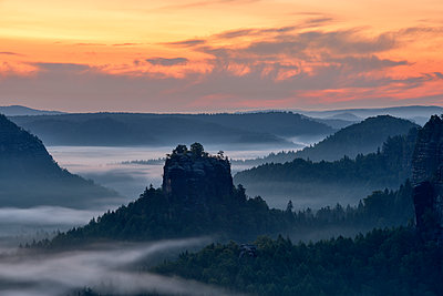 Germany, Saxony, Elbe Sandstone Mountains, view to the mountain Winterstein from the Gleitmannshorn at sunrise - p300m2103538 by Martin Rügner