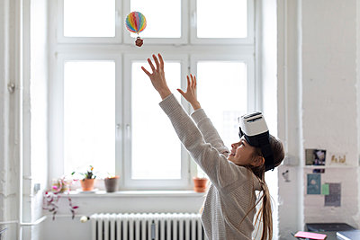 Girl with VR glasses trying to catch hot-air balloon in office - p300m2156046 by Gustafsson