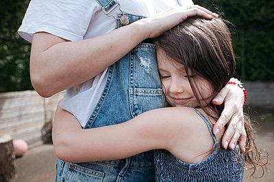 Girl hugging mother at back yard on sunny day - p300m2214039 by Ekaterina Yakunina