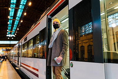 Mid adult man wearing face mask stepping out of train with coffee cup and luggage on station - p300m2251072 by Ezequiel Giménez