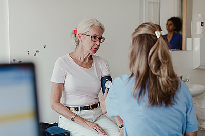 Female doctor checking blood pressure of senior woman in clinic - p426m2135488 by Maskot