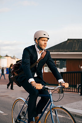Confident businessman riding bicycle on street in city - p426m2145604 by Maskot