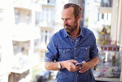Mann mit Smartphone auf dem Balkon - p788m1424716 von Lisa Krechting